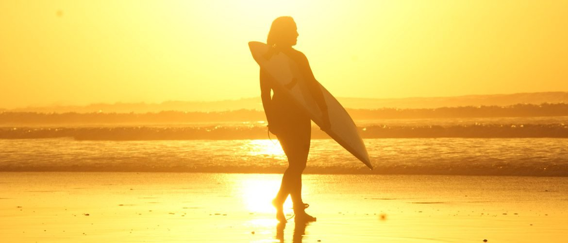 Camino Surfcamp Marokko Surfer Girl with Surfboard on the beach at sunset