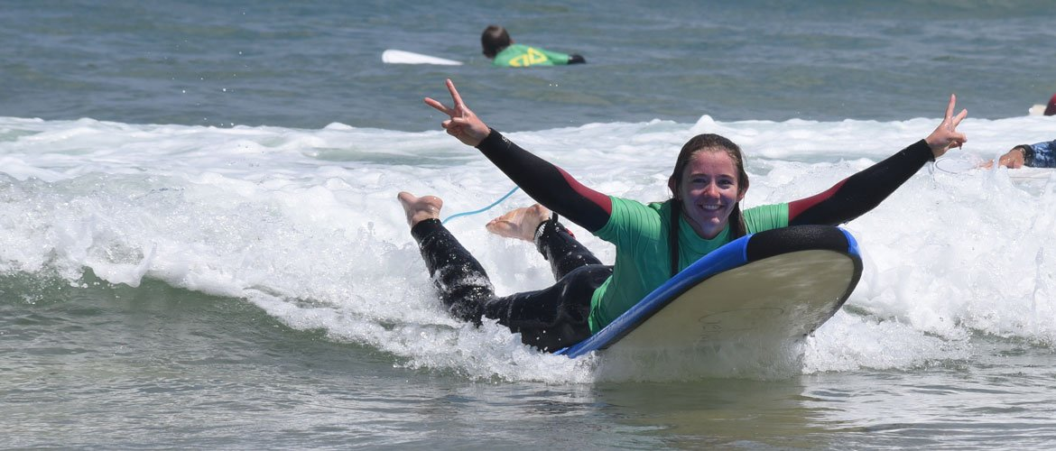 Camino Surfcamp Spain Galicia happy Beginner Surfer With two hands showing victory sign