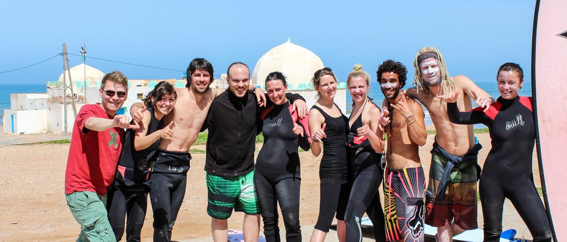 Camino Surfcamp Marokko Surfer Crew Smiling With Mosque in Bakground DE