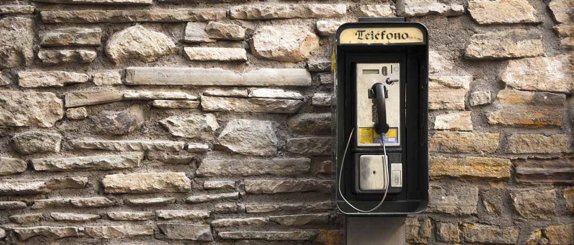 Old spanish telefone on a brick wall - EN